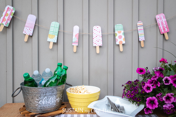 Colorful paper popsicle garland decor hung against a grey wall.