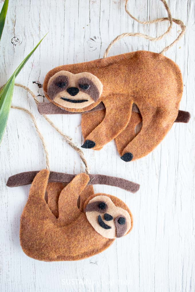 Finished felt no-sew sloth craft with one sleeping sloth and one hanging sloth.