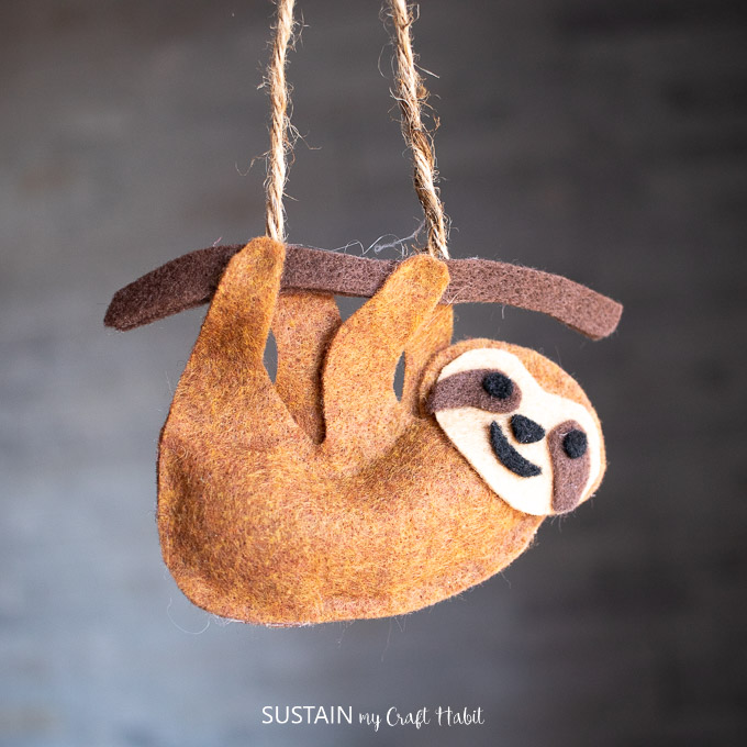 Finished craft with no-sew felt sloth hanging from a piece of twine.