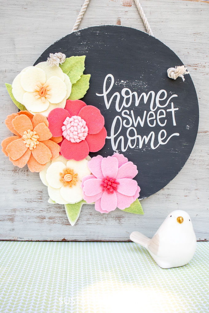"A round dark gray painted wood sign with colorful felt flowers on one side and the handlettered phrase ""home sweet home"" on the other."