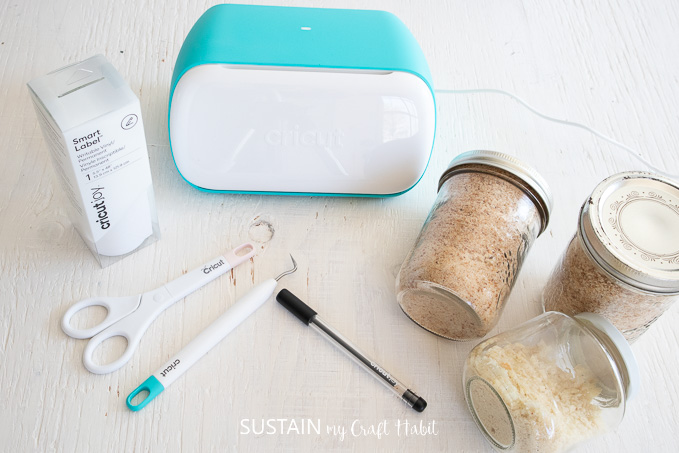 Materials needed to make mason jar labels, including a Cricut joy machine, mason jars, Cricut writable vinyl, Cricut tools and a pen.