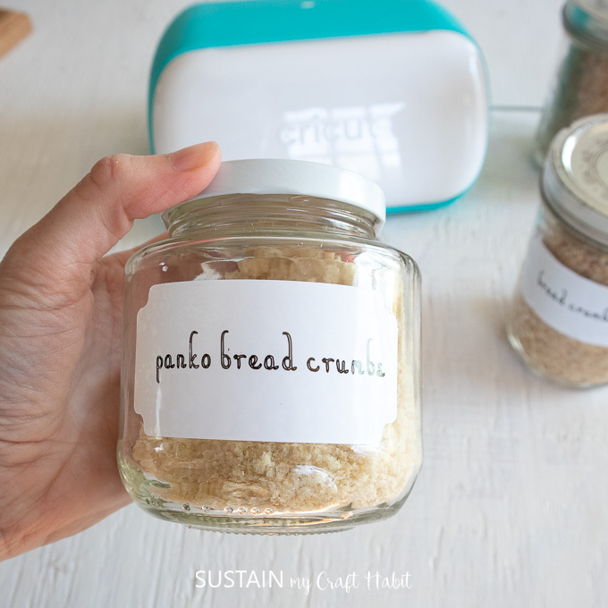 Holding a mason jar filled with breadcrumbs and labeled with a sticker.