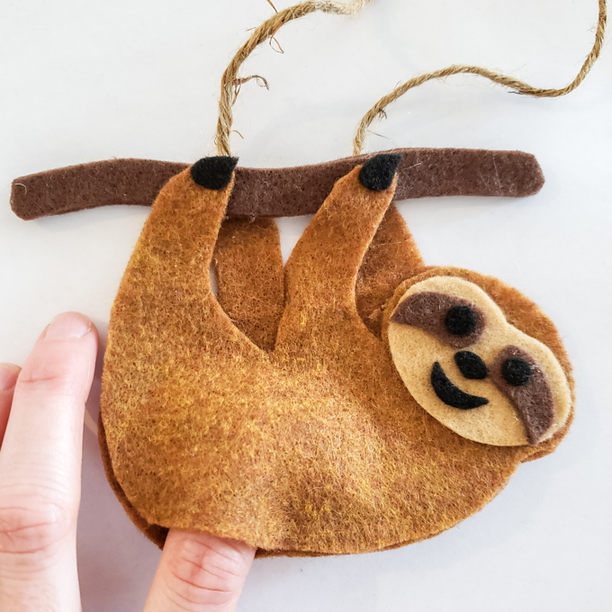 Inserting badding with a finger to the opening of the sloth felt ornament.