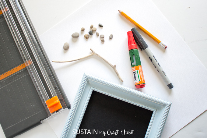 Materials needed to make pebble art including pebbles, twigs, picture frame, paper cutter, glue and pens.