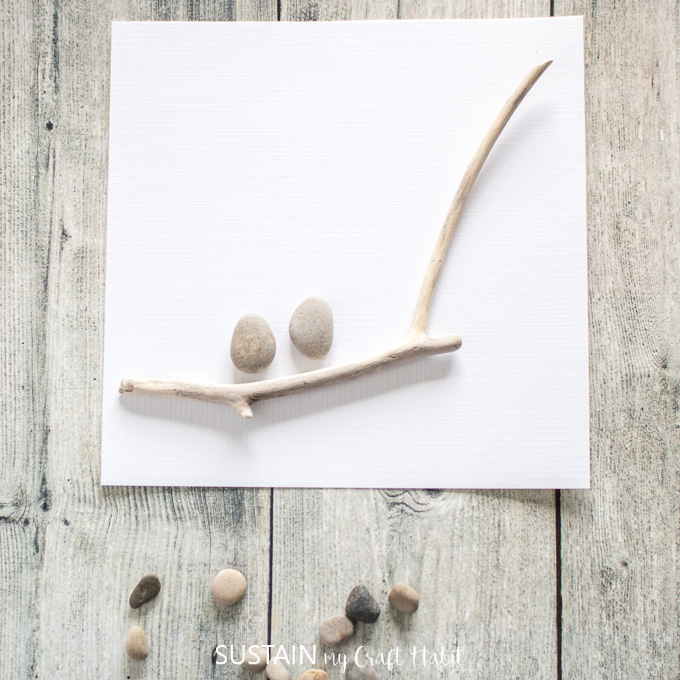 Placing the larger sized pebbles above the twig.