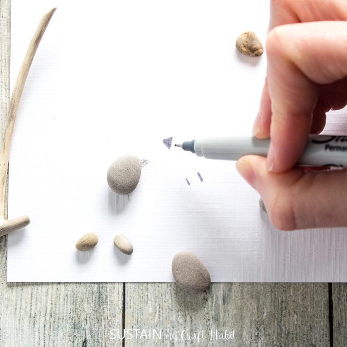 Using a black sharpie to draw the bird beaks and bird feet.