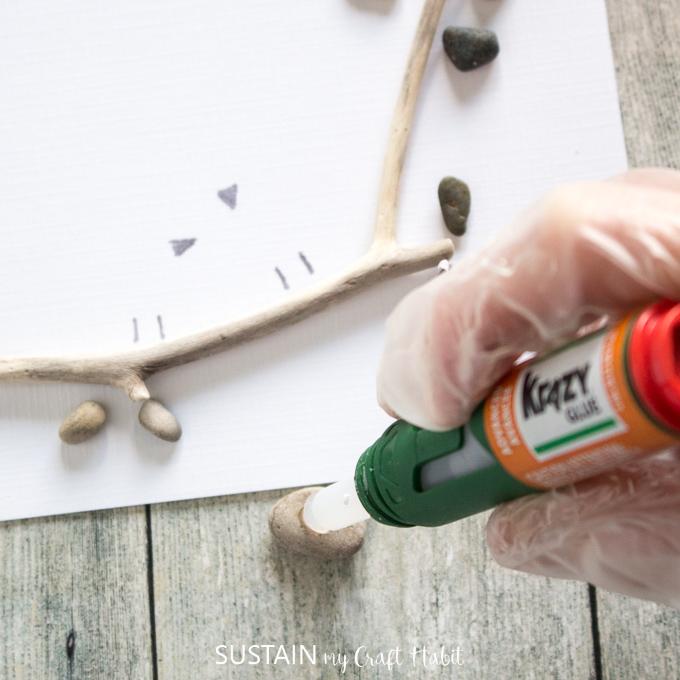 Adding Krazy glue to a pebble.