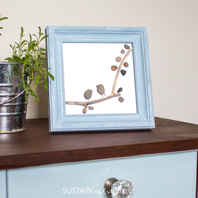 Completed pebble art in a small blue frame on a dark wood surface. A mall plotted plant is to the left side.