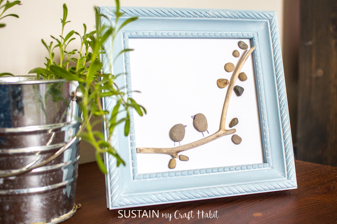 Close up of a blue frame pebble art resembling two birds perched on a tree branch.