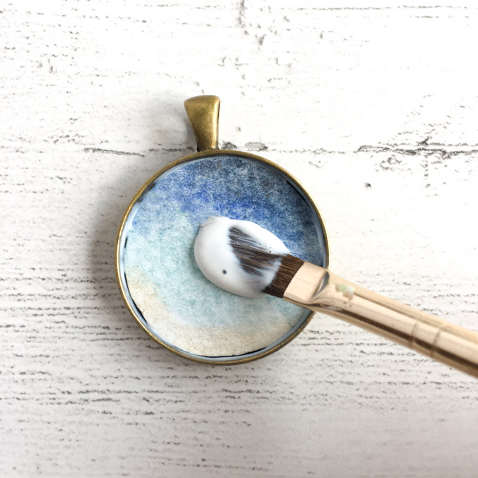 Adding the watercolor image and sealing it onto the bezel jewelry pendant.