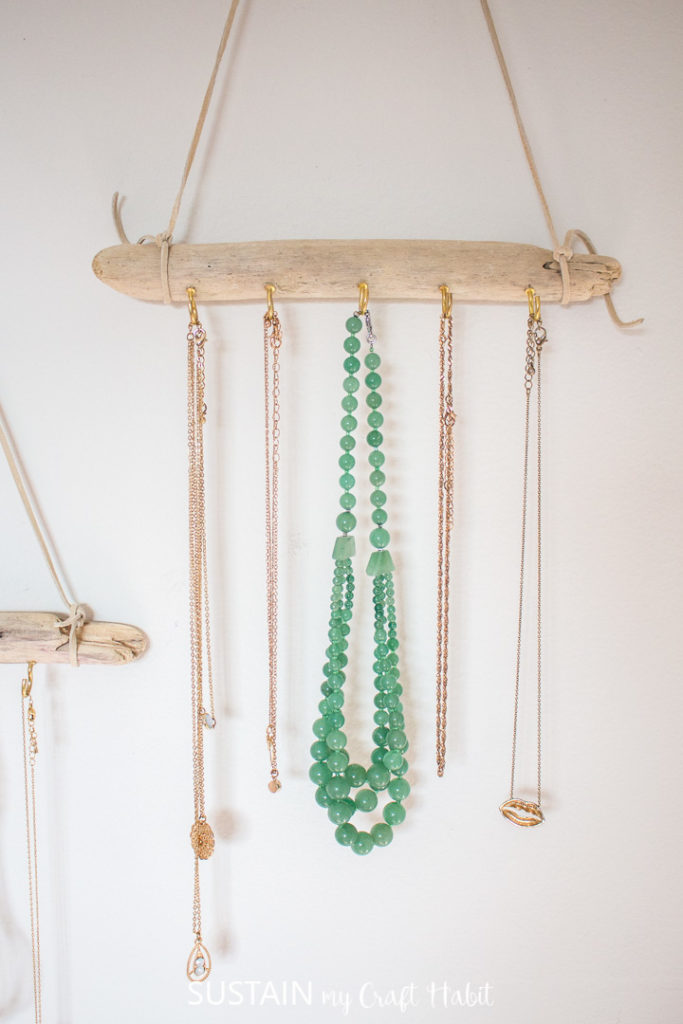 A driftwood jewelry hanger holding necklaces.