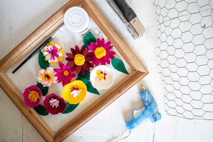 Materials needed to make a photo display including a picture frame, chicken wire, felt flowers, staple gun, paint, paintbrush and glue gun.