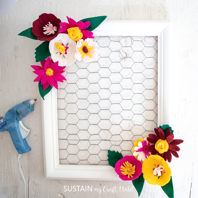 Arranging the felt flowers around the painted picture frame.