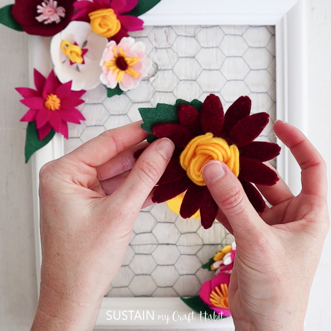 Preparing to glue a felt flower into the picture frame.
