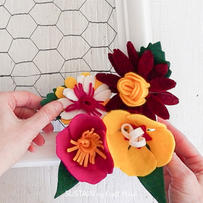 Continuing to glue the felt flowers until they are securely attached together.