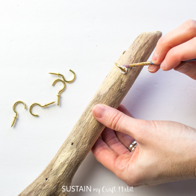 Placing the gold hook in the driftwood and using a brush to remove excess glue.