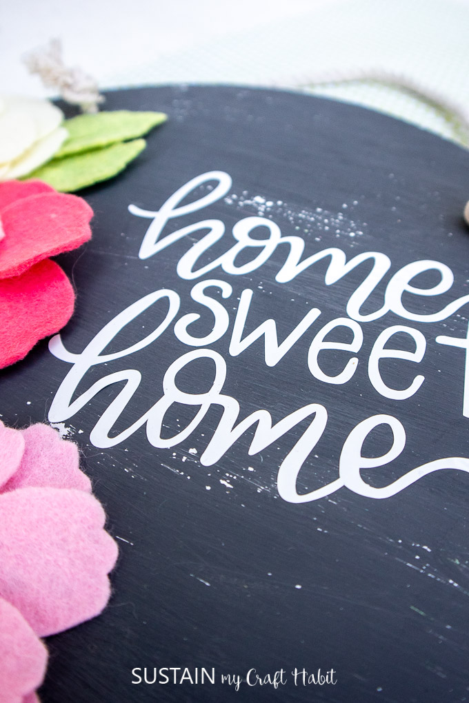 Close up of the home sweet home vinyl on the painted wood sign.