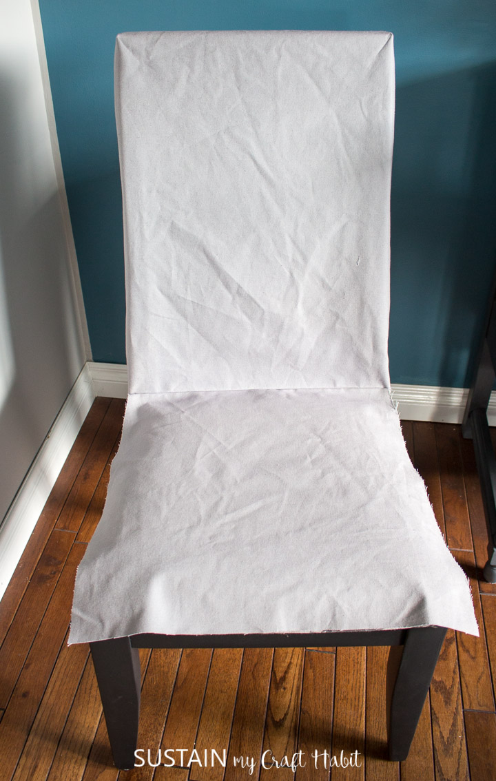 Placing the in-process dining chair slipcover over the chair in order to check the sizing.