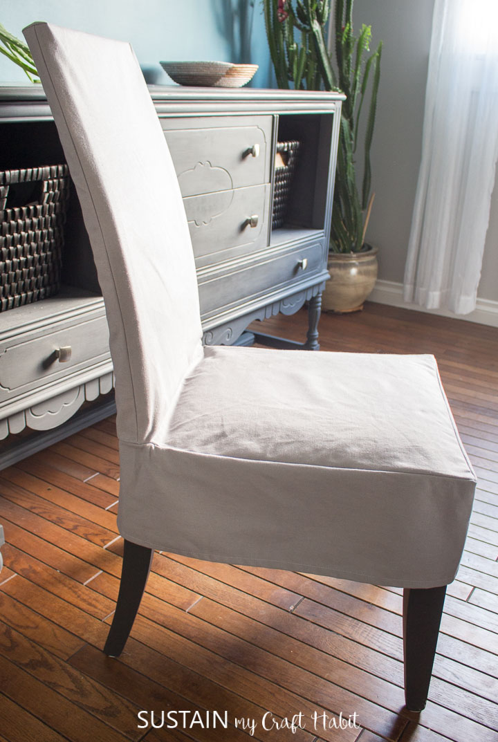 Side view of a completed dining room chair slipcover made from light grey cotton canvas.