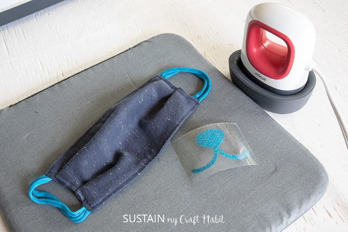 place reusable fabric face mask on Cricut EasyPress mat and preheat EasyPress