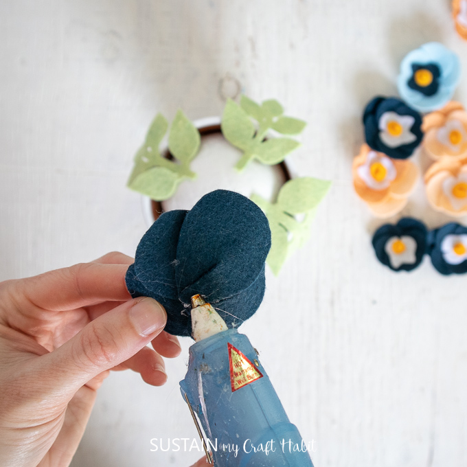 Gluing the back of a felt pansy flower