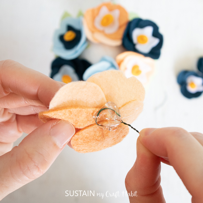 Gluing floral wire to the back of a felt pansy flower.