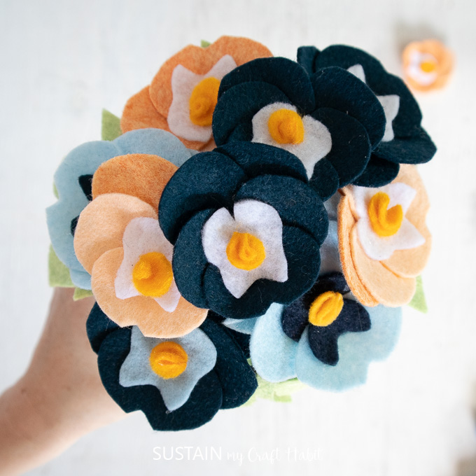 Felt pansies attached to a Styrofoam ball to look like a bouquet.