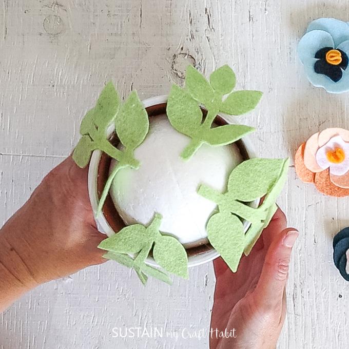 Gluing felt foliage onto the Styrofoam ball.