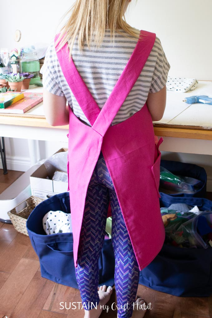 A child wearing a pink apron wihile doing crafts, showing the back of the apron with a cross back style.