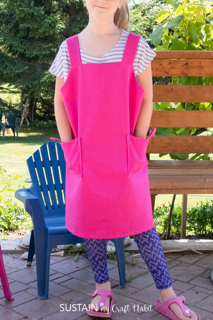 A child wearing a pink kid's apron.