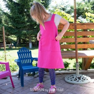 9 year old girl modelling versatile kids apron made with sewing pattern