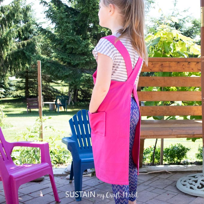 Side view of a child wearing the pink apron.
