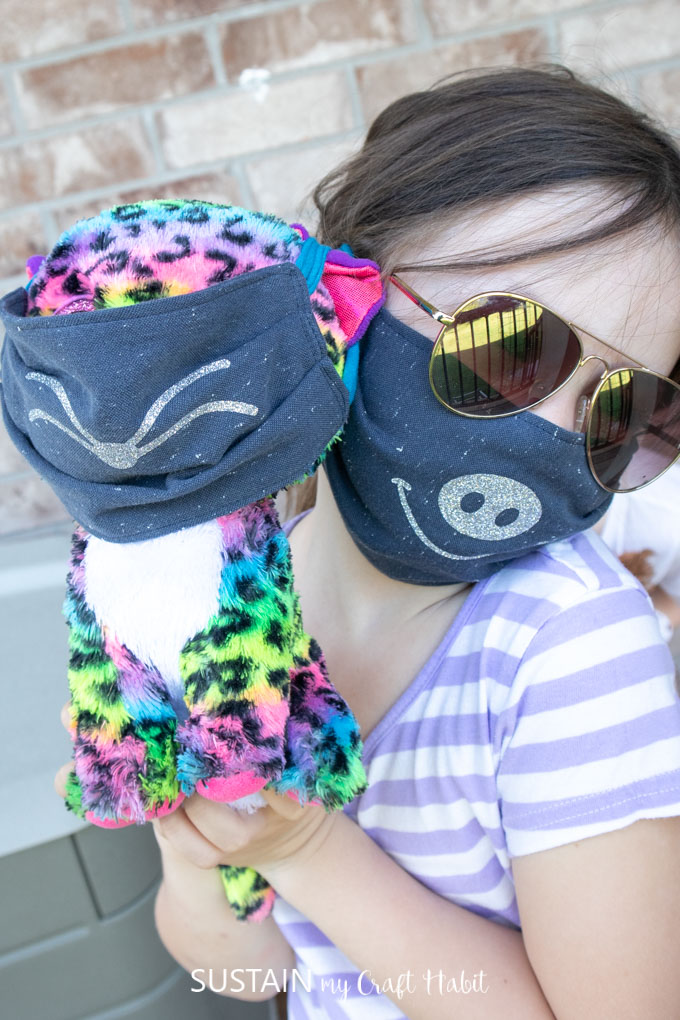 child wearing fabric face mask holding stuffie also wearing a fabric face mask