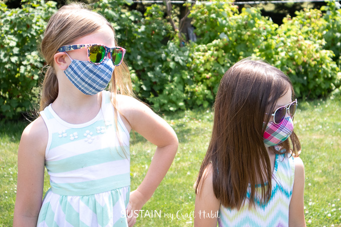 two girls wearing fitted face masks, one girl is 9 years old and the other is 6 years old