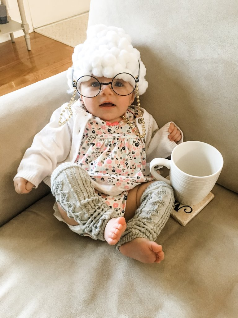 Baby dressed to look like and old lady with a white hair wig and reading glasses.