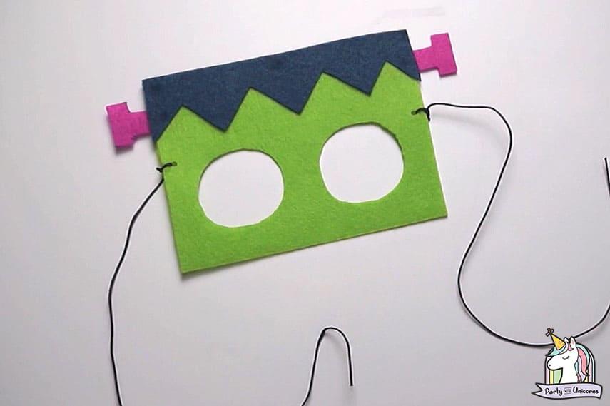A green felt Frankenstein mask on a white surface.