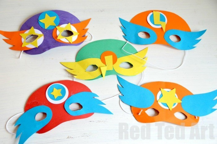 Five colorful superhero masks on a white surface.