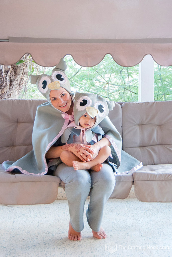 Woman holding a baby wearing matching gray DIY owl costumes.