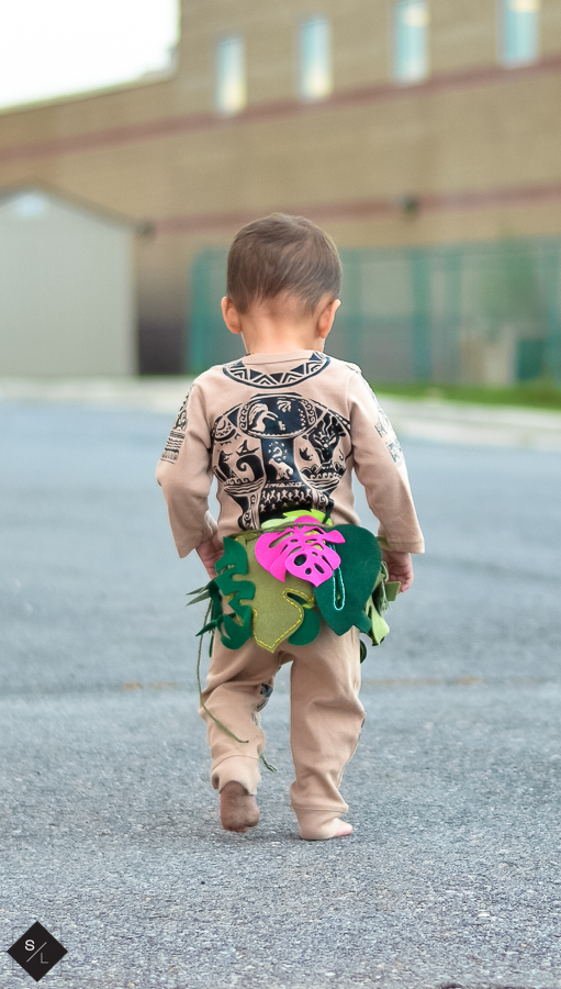 Back view of a toddler wearing a onesie made to look like Disney's Maui character.