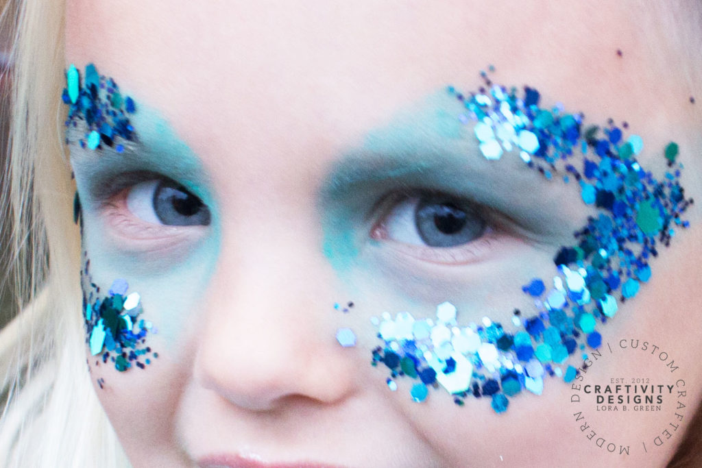Close up image of a child's eyes with blue glitter makeup applied to look like a mermaid.