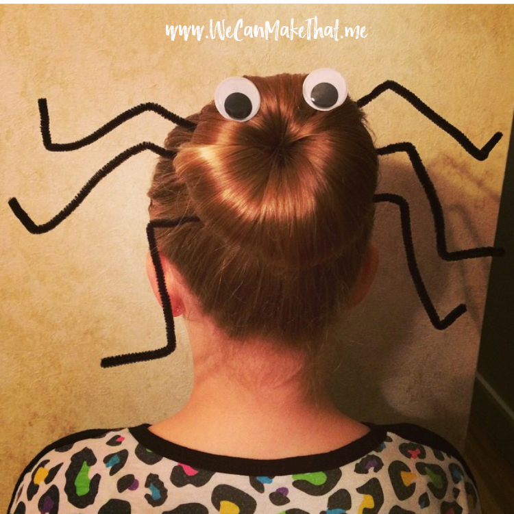 Back view of a child's head with a bun, pipe cleaners and googly eyes shaped to look like a spider.