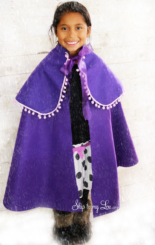 Girl wearing a cute DIY Halloween costume that's a purple Frozen-movie inspired cape.