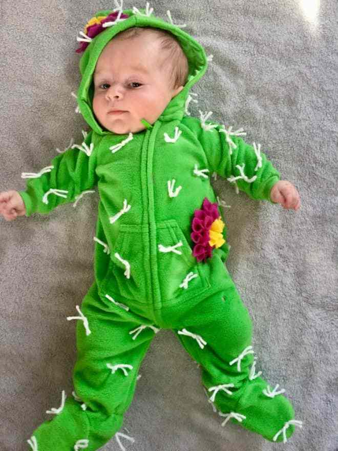 Baby wearing a green onesie with embellishments to look like a little cactus.