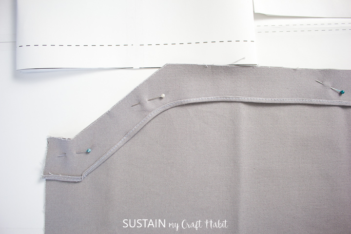 pinning the pocket facing piece to the apron piece along bottom edge for sewing