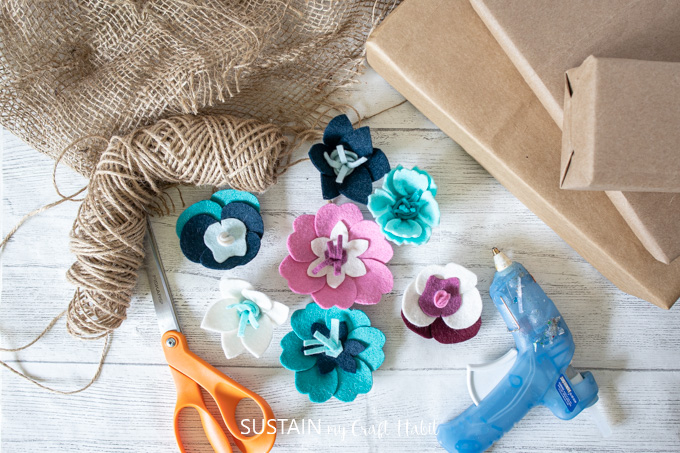 Materials needed to adorn gift packages with felt flowers.