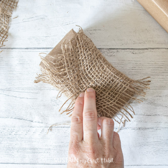 Wrapping burlap around a brown paper package.