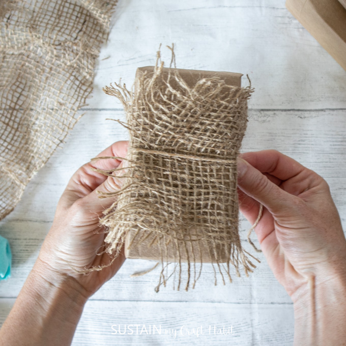 Wrapping twine around the burlap.