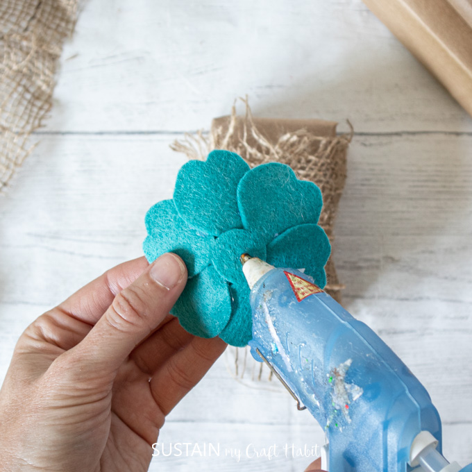 Adding hot glue to the back of a blue felt flower.
