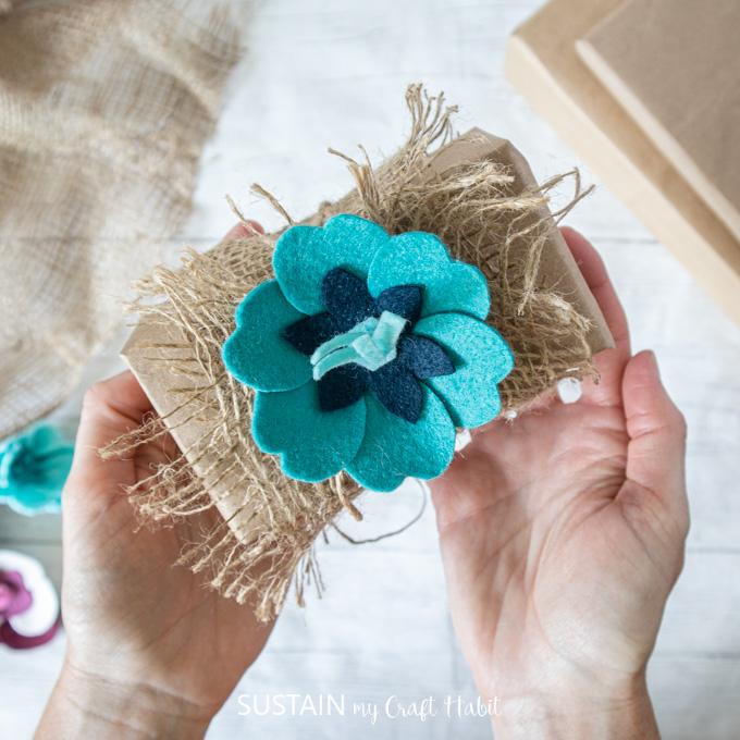 Gluing the blue felt flower onto the burlap.