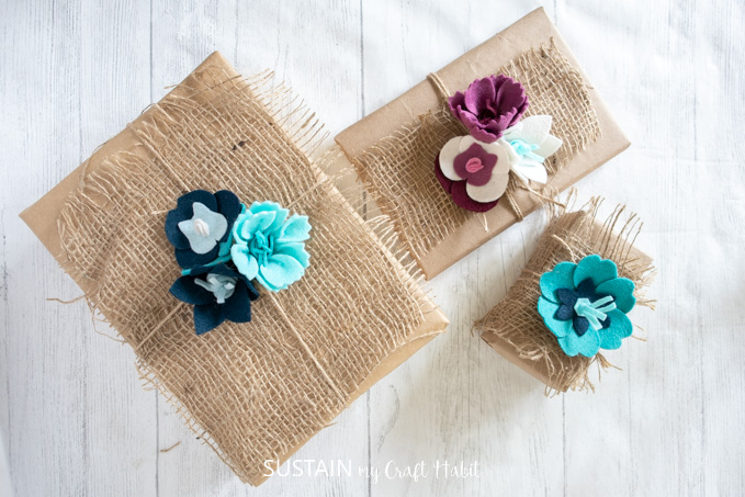 Gifts wrapped with brown paper, burlap and twine with the top adorned with felt flowers.
